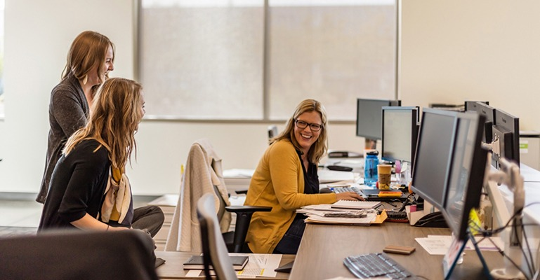 A female office worker seated at her desk looks over her shoulder to smile and laugh with two colleagues behind her.